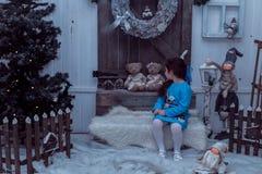 La piccola ragazza felice in vestito con il presente ha un natale Immagine Stock