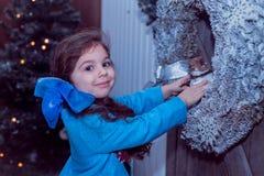 La piccola ragazza felice in vestito con il presente ha un natale Fotografia Stock