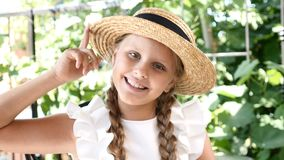 La piccola ragazza graziosa si diverte con suo sorridere del cappello di paglia lifestyle La ragazza gode del giorno di estate e  archivi video