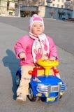 La piccola ragazza graziosa si siede sull'automobile del giocattolo. Fotografie Stock Libere da Diritti