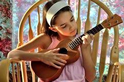 La piccola ragazza ispana gioca le ukulele Immagini Stock