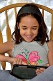 La piccola ragazza ispana gode della sua nuova compressa Fotografie Stock
