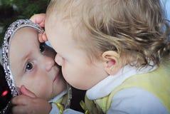 La piccola ragazza lo esamina in specchio Fotografia Stock