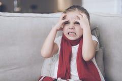 La piccola ragazza malata si siede su uno strato bianco avvolto in una sciarpa rossa Ha un'emicrania e molto una febbre alta Immagine Stock