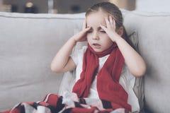 La piccola ragazza malata si siede su uno strato bianco avvolto in una sciarpa rossa Ha un'emicrania e molto una febbre alta Immagini Stock