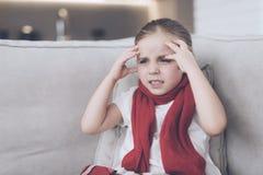 La piccola ragazza malata si siede su uno strato bianco avvolto in una sciarpa rossa Ha un'emicrania e molto una febbre alta Fotografie Stock