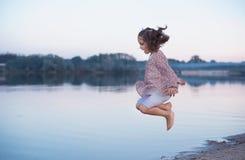 La piccola ragazza salta sopra l'acqua del lago Sport puerili fotografia stock libera da diritti