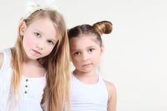 La piccola ragazza seria due in vestiti bianchi esamina la macchina fotografica Fotografia Stock Libera da Diritti