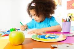 La piccola ragazza si siede alle lettere di scrittura e della tavola Immagine Stock