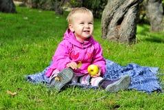 La piccola ragazza si siede sul glade verde Fotografia Stock