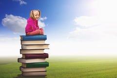 La piccola ragazza si siede sul mucchio dei libri Fotografia Stock Libera da Diritti