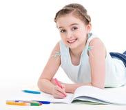 La piccola ragazza sorridente si trova con il libro. Fotografia Stock