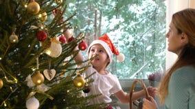 La piccola ragazza sveglia con la sua mamma decora l'albero di Natale video d archivio