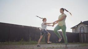 La piccola ragazza sveglia e sua madre che filano intorno tenersi per mano nel cortile La donna ed il bambino divertendosi dentro stock footage