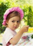 La piccola ragazza sveglia ha una prima colazione in caffè all'aperto Immagini Stock Libere da Diritti