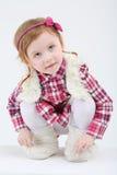 La piccola ragazza sveglia nella maglia e negli stivali della pelliccia si siede e cerca Fotografia Stock