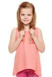 La piccola ragazza sveglia in una camicia rosa si tiene per mano i capelli, isolati su fondo bianco Immagini Stock Libere da Diritti
