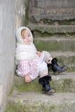 La piccola ragazza triste in una sciarpa bianca si siede Fotografia Stock Libera da Diritti
