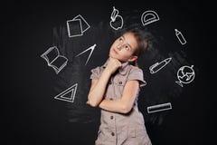 La piccola ragazza vicino alla lavagna pensa alle materie d'insegnamento Immagine Stock Libera da Diritti
