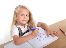La piccola scolara che si siede l'aggiunta felice numera nel concetto di istruzione dei bambini Fotografia Stock