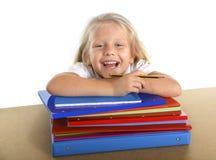 La piccola scolara sveglia felice sullo scrittorio che pende dentro si rilassa sui libri Immagine Stock
