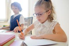 La piccola scolara sveglia in vetri qualcosa scrive diligente in un quaderno Fotografia Stock