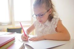 La piccola scolara sveglia in vetri qualcosa scrive diligente in un taccuino Immagine Stock Libera da Diritti