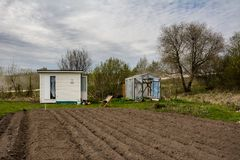 La piccola serra con le porte si è aperta, piccoli casa estiva e armch Fotografia Stock Libera da Diritti