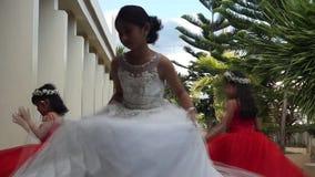 La piccola sposa e le piccole domestiche del ` s della sposa restano e giocano al sagrato mentre la cerimonia di nozze sta accend stock footage