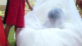 La piccola sposa e le piccole domestiche del ` s della sposa restano e giocano al sagrato mentre la cerimonia di nozze sta accend archivi video
