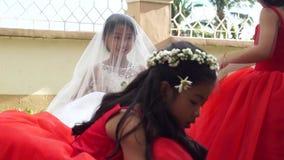 La piccola sposa e le piccole domestiche del ` s della sposa restano e giocano al sagrato mentre la cerimonia di nozze sta accend video d archivio