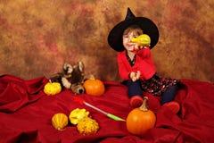 La piccola strega sta divertendosi per Halloween con le zucche ed il cappello Fotografia Stock