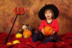 La piccola strega sta divertendosi per Halloween con le zucche ed il cappello Immagine Stock Libera da Diritti
