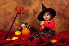 La piccola strega sta divertendosi per Halloween con le zucche ed il cappello Immagini Stock Libere da Diritti
