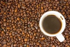 La piccola tazza bianca di caffè preparato con vapore sopra che sta su un fondo di marrone sparso ha arrostito i chicchi di caffè Fotografia Stock