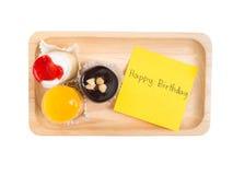 La piccola tazza sveglia agglutina sul vassoio di legno con la parola di buon compleanno Immagini Stock
