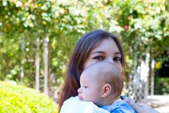 La piccola testa del bambino dal profilo sulla spalla di giovane madre, mamma graziosa con compone sugli occhi sta tenendo il bam immagine stock