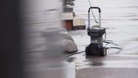 La piccola unità automatica della pompa con i tubi flessibili collegati è disposta sulla terra dell'asfalto archivi video