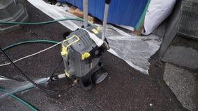 La piccola unità meccanica della pompa con i tubi flessibili collegati è disposta sulla terra dell'asfalto archivi video