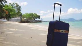 La piccola valigia blu sta sulla riva di bello mare, di un concetto atteso da tempo di svago, di un viaggio e di un concetto di s stock footage