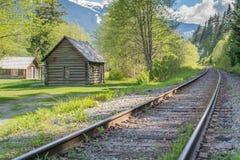 La piccola vecchia capanna accanto al treno segue la conduzione nella distanza Fotografia Stock Libera da Diritti
