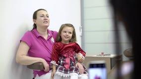 La piccoli ragazza e dentista aggiustano la foto sul telefono cellulare video d archivio
