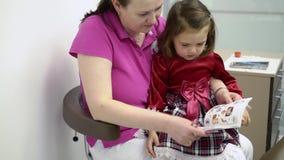 La piccoli ragazza e dentista aggiustano i libri di sorveglianza con gli autoadesivi video d archivio