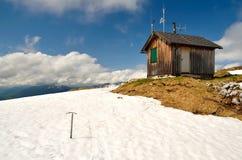 La piccozza da ghiaccio ha attaccato nella neve accanto alla capanna di legno in montagne Fotografia Stock Libera da Diritti