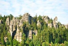 La piedra arenisca de la ciudad de la roca de Adrspach se eleva con los árboles forestales verdes Foto de archivo libre de regalías