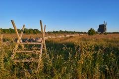 La piedra caliza de Alvar amarra con la cerca y el molino en la puesta del sol imágenes de archivo libres de regalías