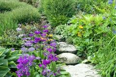 La piedra del jardín de la cabaña camina entre las flores del verano y las plantas imagen de archivo libre de regalías