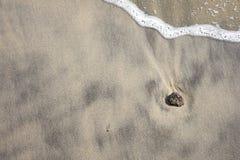 La piedra en la playa con la onda del mar Fotos de archivo libres de regalías