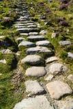 La piedra señaló pasos por medio de una bandera en la trayectoria Imágenes de archivo libres de regalías