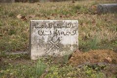 La piedra sepulcral vieja con la cruz y el árabe les gusta escribir Fotos de archivo libres de regalías
